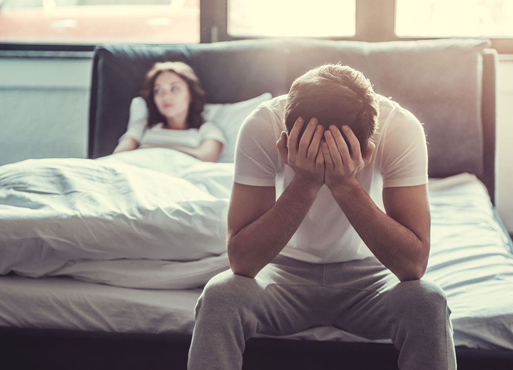 Man sitting on edge of bed frustrated with head in hands while woman in bed looks away.