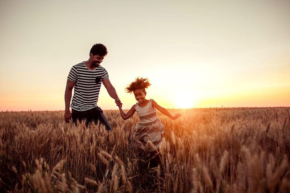 Father being led by daughter through a field.