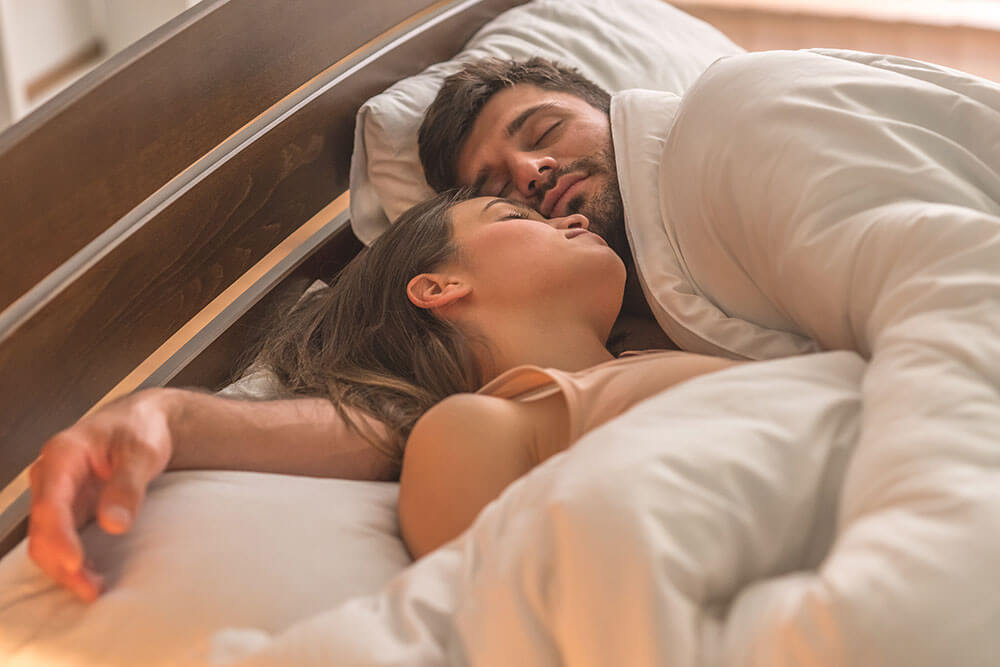 Couple sleeping peacefully in a bed.